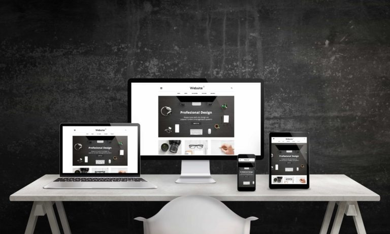 Responsive web site promotion on computer display, laptop, tablet and smart phone. Modern, clean web design. White office desk with devices, black wall in background.